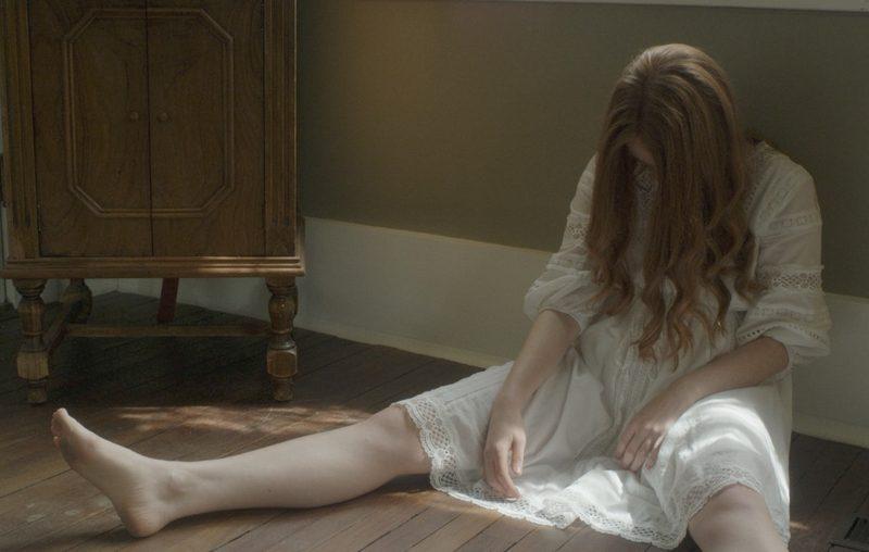 Amber Broken Doll Sitting on Floor