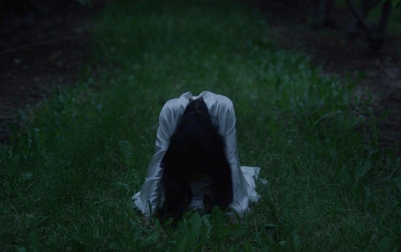 Ghostly Woman in Orchard Kneeling Head Down Still
